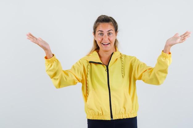 Junge frau, die um sich herum zeigt, während sie ihre hände im gelben regenmantel erhebt und froh aussieht
