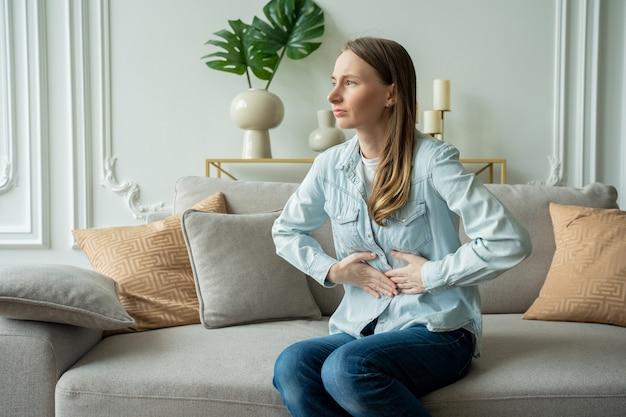 Junge frau, die unter bauchschmerzen beim sitzen auf sofa zu hause leidet