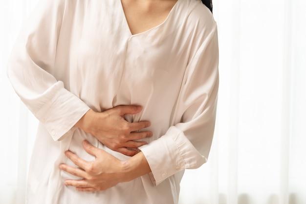 Junge frau, die unter den bauchschmerzen glauben magenschmerzen, symptom von pms leidet