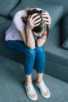 Junge frau, die unter den kopfschmerzen sitzen auf sofa leidet