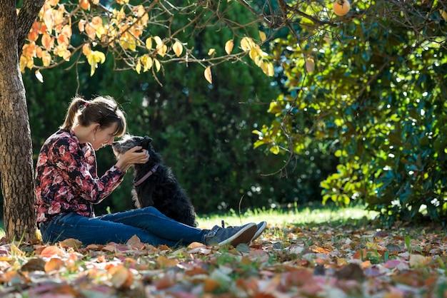 Junge frau, die unter einem bunten herbstbaum sitzt, der ihren schwarzen hund liebevoll streichelt