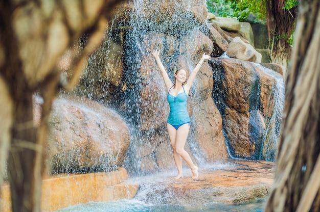 Junge frau, die unter einem wasserfall im aquapark entspannt