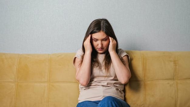 Junge frau, die unter kopfschmerzen leidet, während sie auf dem sofa sitzt.