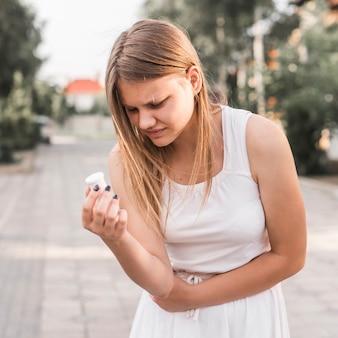 Junge frau, die unter magenschmerzen hält tablettenfläschchen leidet