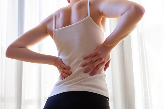 Junge frau, die unter nackenschmerzen und rückenschmerzen leidet und die muskeln dehnt.