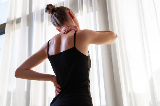 Junge frau, die unter nackenschmerzen und rückenschmerzen leidet und die muskeln zu hause streckt. rücken- und nackenschmerzen frau