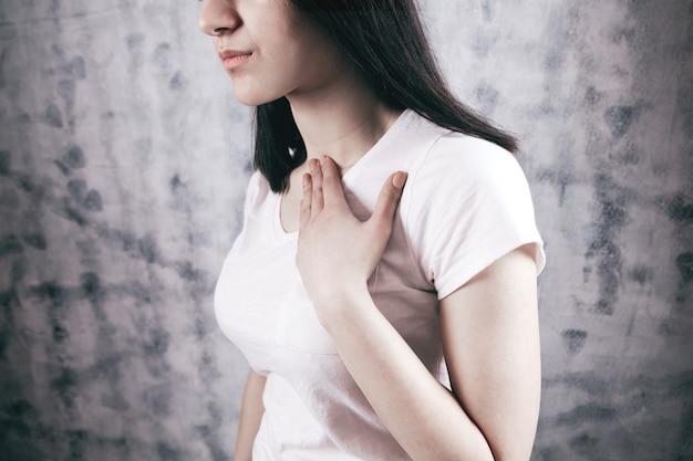 Junge frau, die unter starken brustschmerzen leidet