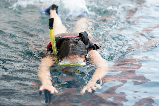 Junge frau, die unter wasser in den tragenden schnorchel- und unterwasseratemgerätschuhen des pools schwimmt