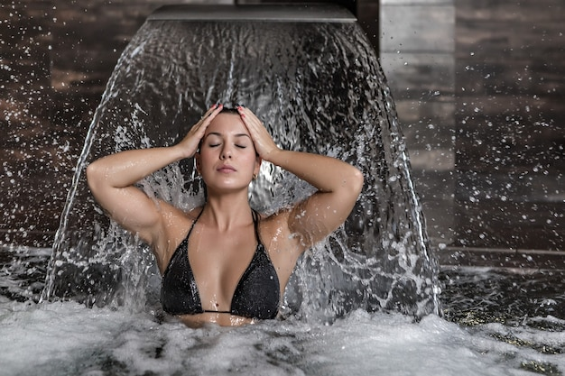 Junge frau, die unter wasserstrom im spa-zentrum erfrischt