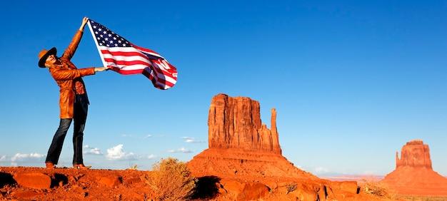 Junge frau, die usa-flagge am monument valley hält