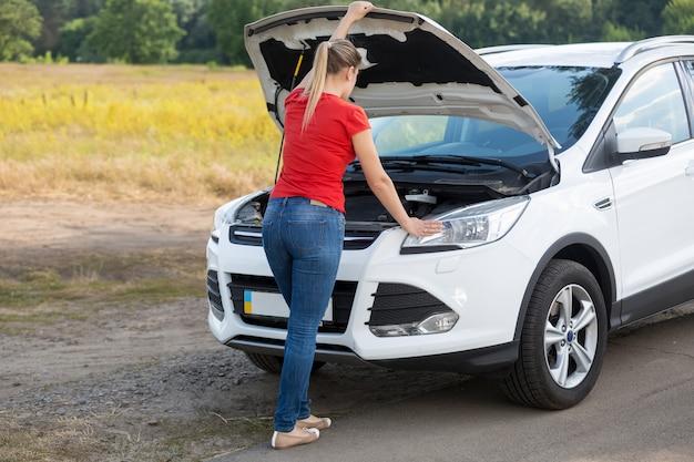Junge frau, die versucht, ein kaputtes auto auf dem land zu reparieren?