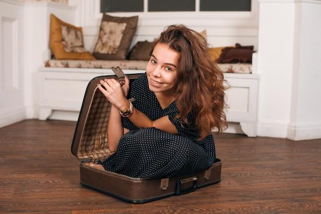 Junge frau, die versucht, in einen koffer zu klettern.