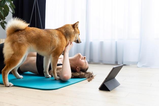 Junge frau, die versucht, neben ihrem hund zu trainieren