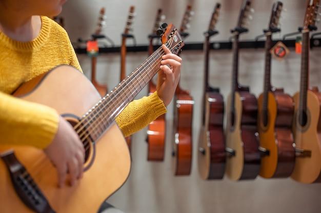 Junge frau, die versucht und kauft eine neue hölzerne gitarre im instrumental- oder musikgeschäft, instrumentenkonzept