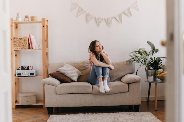 Junge frau, die verträumt auf sofa in ihrer hellen wohnung sitzend aufwirft