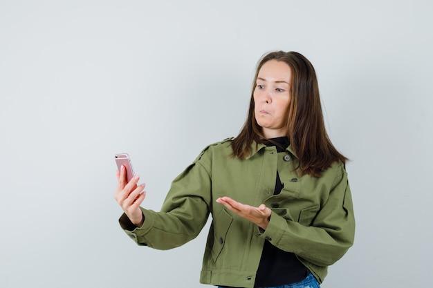 Junge frau, die videoanruf macht, während sie ihre offene handfläche in der grünen jacke anhebt und verblüfft, vorderansicht schaut.