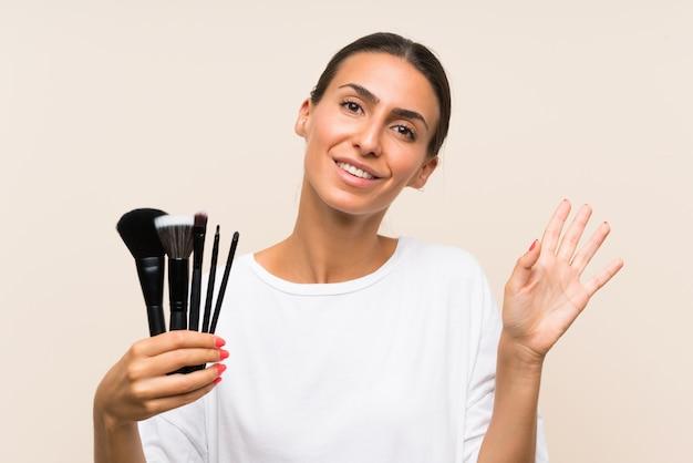 Junge frau, die viel make-upbürste begrüßt mit der hand mit glücklichem ausdruck hält