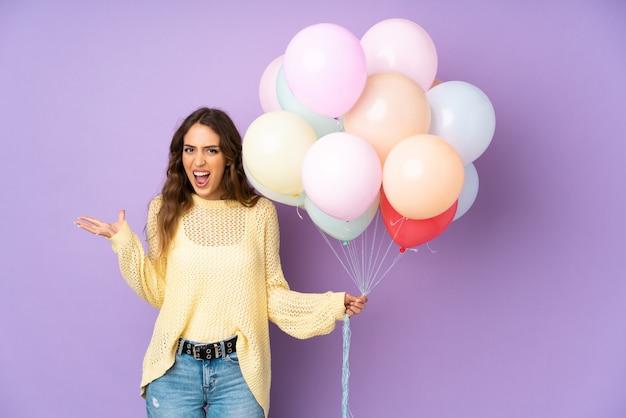 Junge frau, die viele ballone auf unglücklichem und mit etwas frustriert fängt