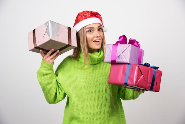 Junge frau, die viele festliche weihnachtsgeschenke hält.