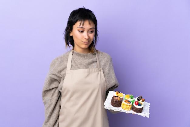 Junge frau, die viele verschiedene minikuchen über isoliertem lila raum hält, der zur seite steht und schaut