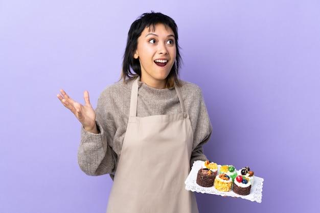 Junge frau, die viele verschiedene minikuchen über isoliertem purpur mit überraschendem gesichtsausdruck hält