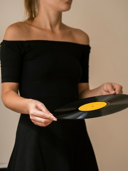 Junge frau, die vinylaufzeichnungsscheibe hält