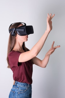 Junge frau, die virtual-reality-brillen-headset, vr-box trägt. verbindung, technologie, neue generation, fortschrittskonzept. mädchen, das versucht, objekte in der virtuellen realität zu berühren. studioaufnahme auf grau