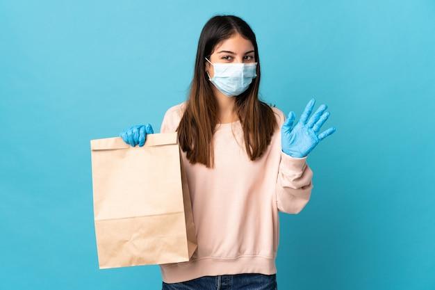 Junge frau, die vom coronavirus mit einer maske schützt und eine einkaufstüte des lebensmittels lokalisiert auf blau salutierend mit hand mit glücklichem ausdruck hält
