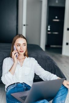 Junge frau, die von zu hause aus arbeitet, auf dem boden sitzt und einen laptop benutzt, mit dem kunden am telefon spricht