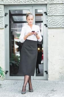 Junge frau, die vor glastür unter verwendung des mobiltelefons steht