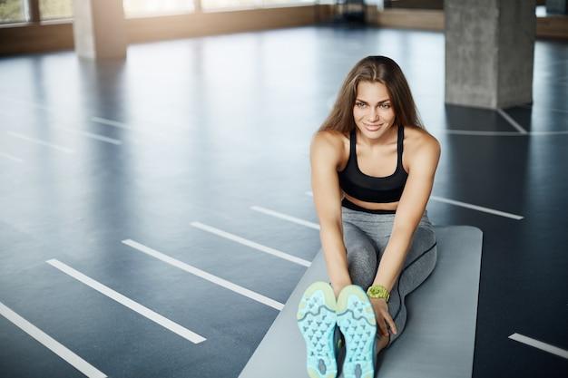 Junge frau, die vor pilates-sitzung streckt. weibliche körperfitnessathletin, die sich aufwärmt.
