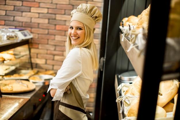 Junge frau, die vor regalen im bäckeryshop und -c $ lächeln aufwirft