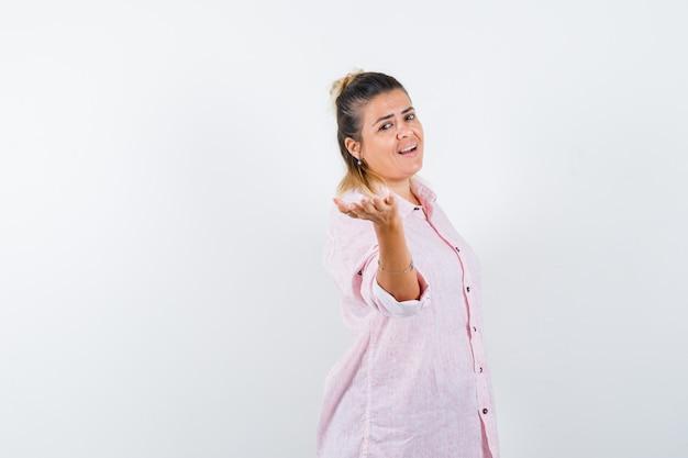 Junge frau, die vorgibt, etwas im rosa hemd anzubieten und fröhlich auszusehen