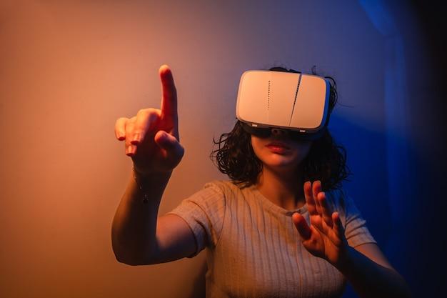 Junge frau, die vr brille trägt. interaktion mit der virtuellen realität. futuristisches umfeld. freizeitbeschäftigung zu hause