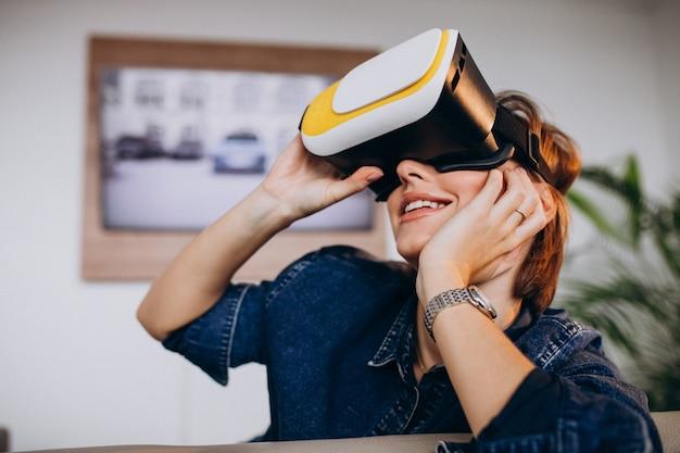 Junge frau, die vr gläser trägt und virtuelles spiel aufpasst