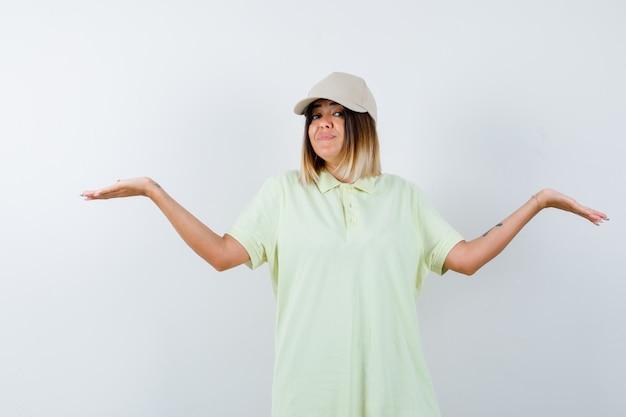 Junge frau, die waage gestikuliert, in t-shirt, mütze und selbstbewusst aussehend. vorderansicht.