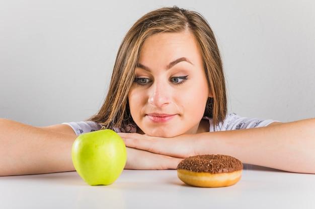 Junge frau, die wählt, um apfel anstelle des donuts zu essen
