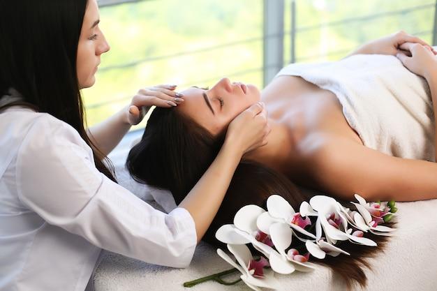 Junge frau, die während der traditionellen thai-massage im spa- und wellnesscenter entspannt.