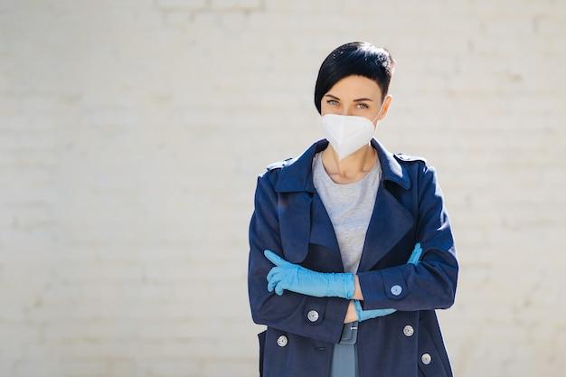 Junge frau, die während des ausbruchs von covid 19 eine medizinische einwegmaske und handschuhe auf der straße trägt. schutz in der prävention des coronavirus