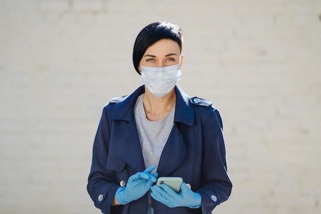 Junge frau, die während des ausbruchs von covid 19 eine medizinische einwegmaske und handschuhe mit smartphone auf der straße trägt. schutz in der prävention des coronavirus. ein konzept der lieferung, online-service, app.