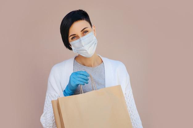 Junge frau, die während des ausbruchs von covid 19 eine medizinische einwegmaske und handschuhe trägt, die eine papiertüte mit einkäufen hält. lieferservice-konzept.