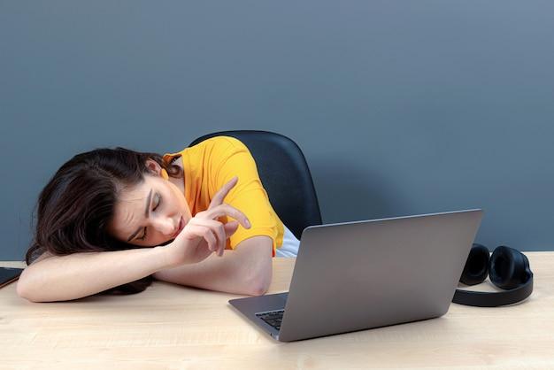Junge frau, die während des langweiligen webinars oder vortrags, des konzepts der online-arbeit oder des studiums am laptop döst
