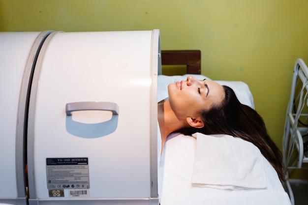 Junge frau, die während des verjüngungsverfahrens auf dem tisch der kosmetikerin liegt