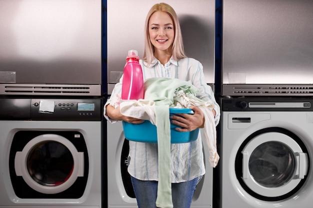 Junge frau, die wäsche am waschsalon tut, schaut auf lächelnde kamera, hält kleidung in den händen und steht nahe waschmaschinen. waschen, reinigen, waschen, hausfrauenkonzept