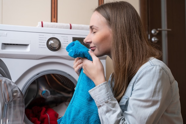 Junge frau, die wäsche in waschmaschine legt, die wäsche unter verwendung der modernen automatischen maschine wäscht