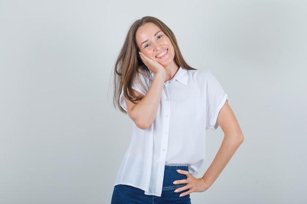 Junge frau, die wange auf erhabener handfläche in weißem t-shirt, jeans und süß aussehend lehnt