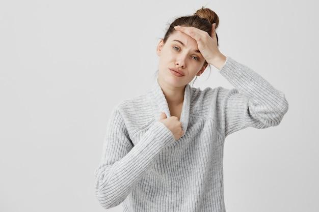 Junge frau, die warmen wollpullover trägt, der heiß ist und ihren kopf berührt, der versucht, sich auszuziehen. weibliche seo-spezialistin, die das gefühl hat, keine frische luft zu haben, drückt unzufriedenheit aus. sensationskonzept