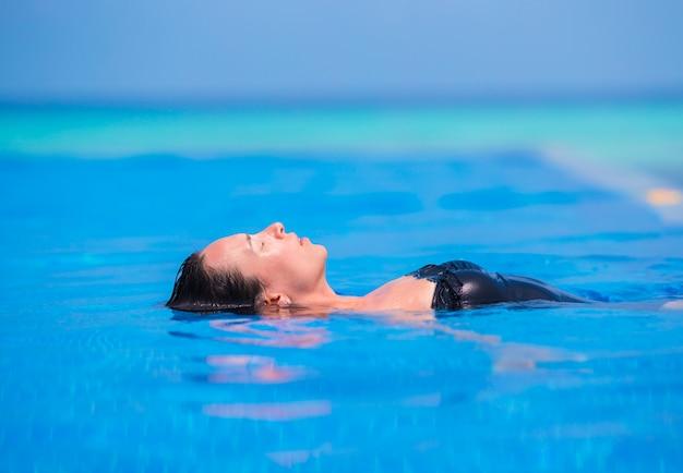 Junge frau, die wasser und sonne swimmingpool im im freien genießt.