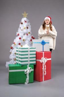 Junge frau, die weihnachten auf grau feiert