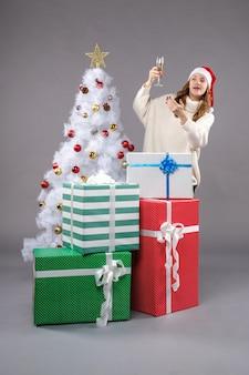 Junge frau, die weihnachten auf grauem boden feiert